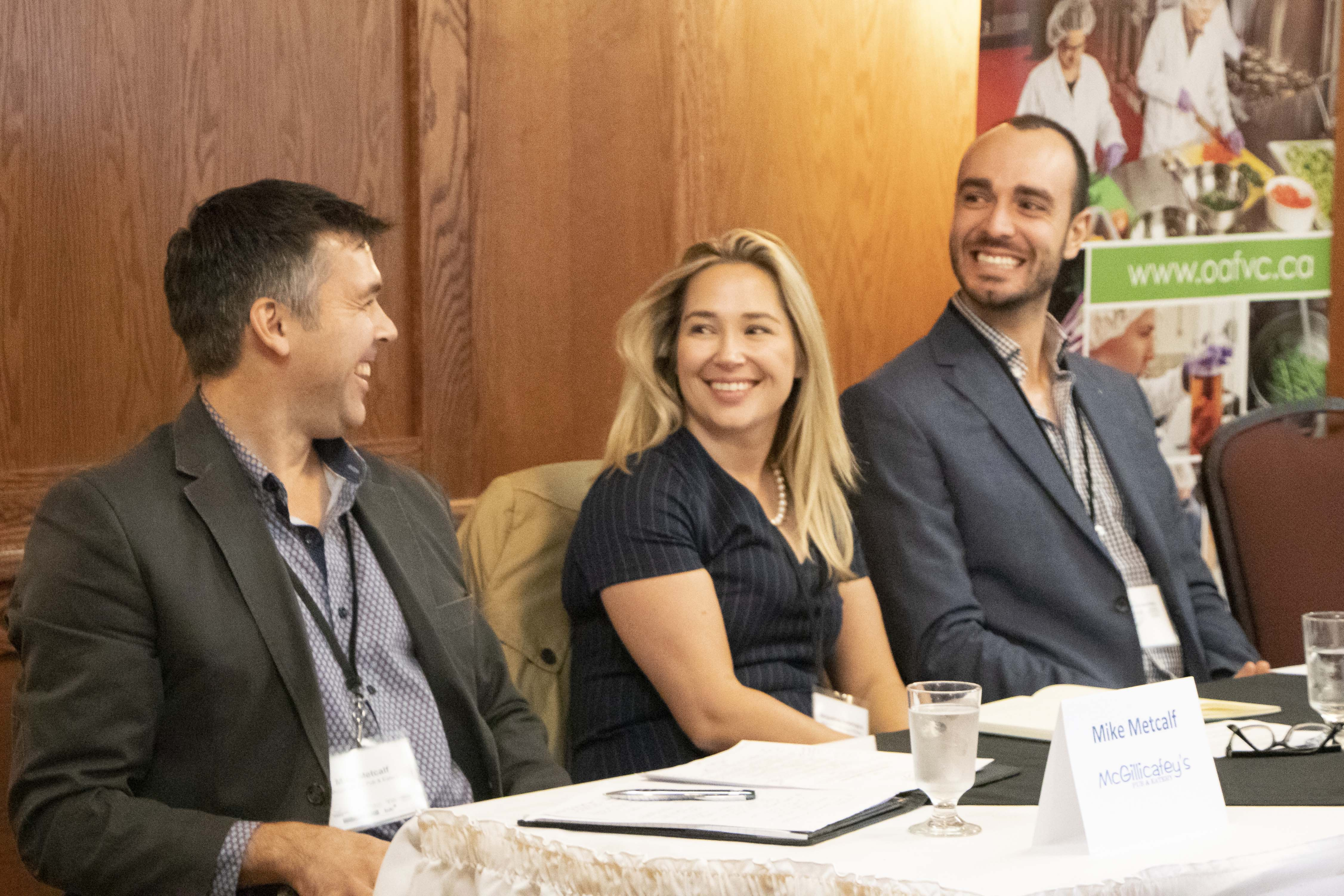 Three small business panelists smile at each other during session
