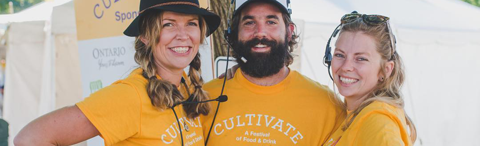 One man, two women, wearing yellow Cultivate t-shirts standing together under tree at event
