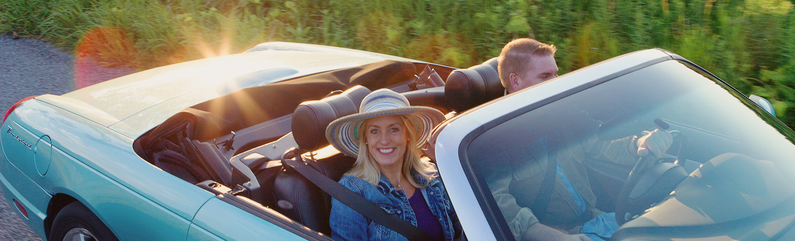 Convertible car with couple in it driving into sunset on country road