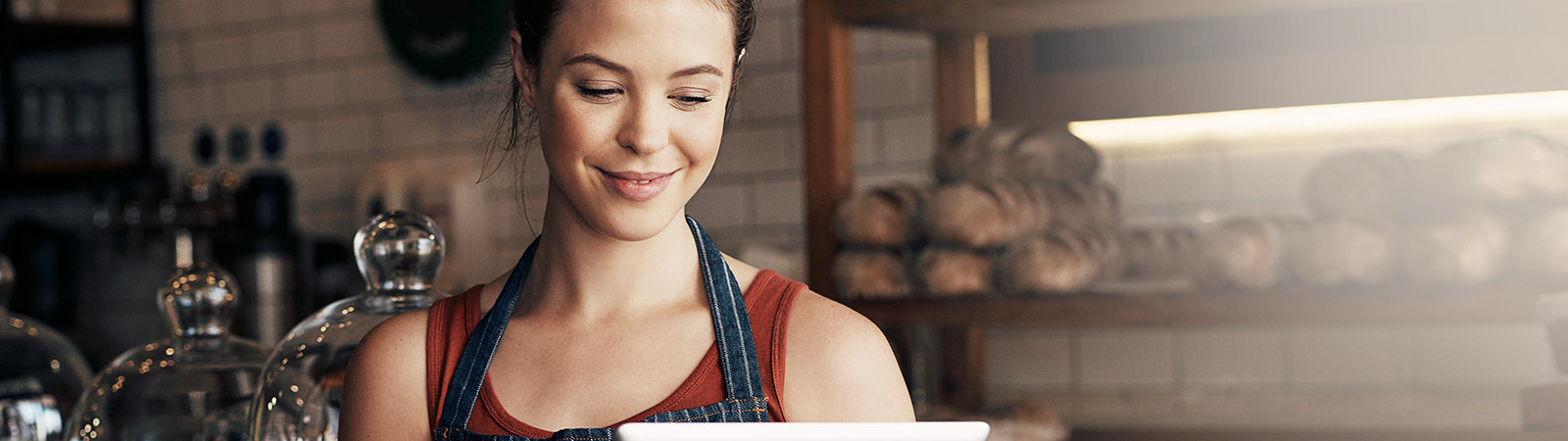 Woman in bakery looking down at iPad smiling