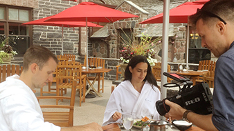Man video recording couple eating salad at table with umbrellas on outdoor patio