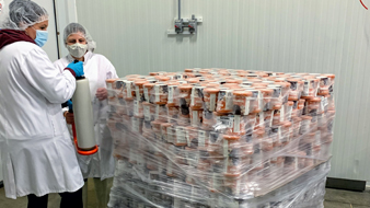2 staff wearing gloves, lab coats and hair nets wrapping a pallet of food
