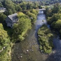 Bird's-eye view of river, trees, old mill and bridge