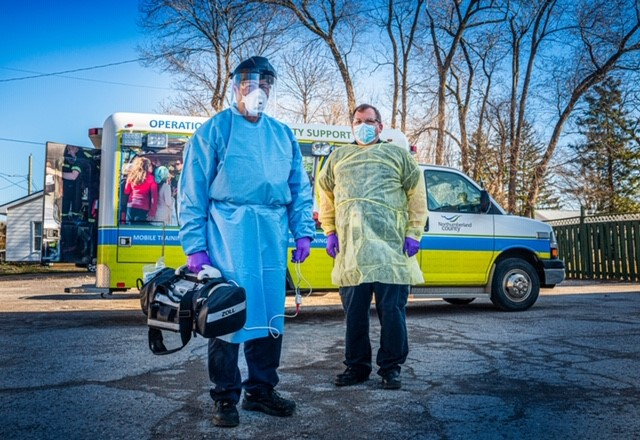 Two paramedics stand in front of ambulance in personal protective equipment
